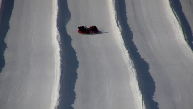 Winter scenic of people tubing down a hill (High Definition) video