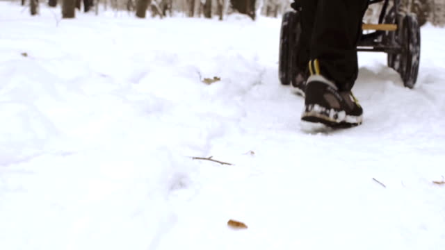 Winter walk through snowy field with baby carriage video