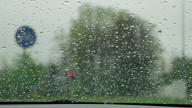 SLOW MOTION CLOSE UP: Wipers wiping raindrops off a windshield video