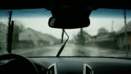 SLOW MOTION: Wiping raindrops off a windshield in a car video