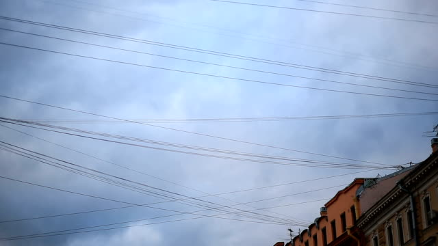 Wires against the background of flying clouds on a blue sky video
