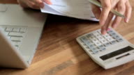Woman Adding Up Domestic Bills With Calculator video