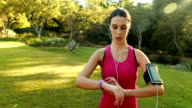 Woman adjusting music settings on armband from smartphone video