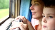 Woman and boy looking at nature from moving railway carriage video