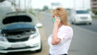 woman and broken car calling for help on cell phone. broken car on the road video