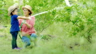 Woman and girl, Mother and Daughter watering a tree together video