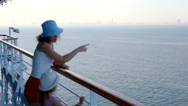 Woman and girl stands on deck of cruise liner video