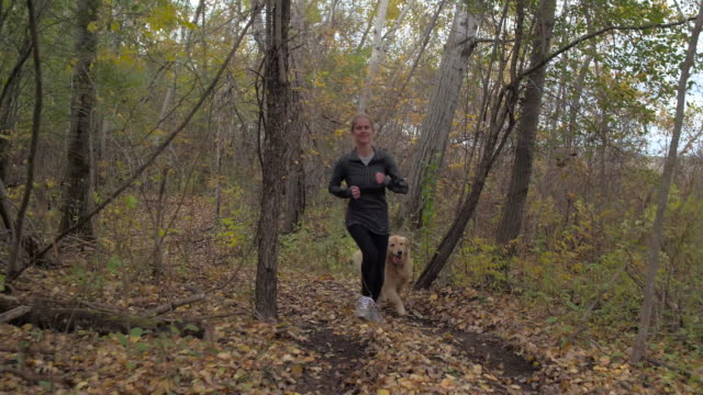 Woman and Her Dog Running Through Forest video