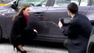 Woman and insurance agent discussing car damage video