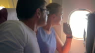 Woman and man looking out plane window video