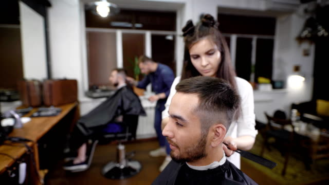 Woman and man making classic stylish hair to male customers in salon video