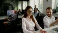 Woman and man satisfied with work. Office interior video