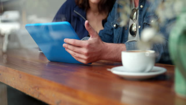 Woman and Man sitting in coffee shop with Tablet video