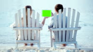 Woman and man sitting on the beach looking at pad with green screen video