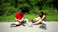 Woman and man sitting on track, putting rollerblades on feet. video