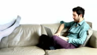Woman and man speaking and relaxing on couch video