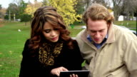 Woman and man with digital tablet in park video