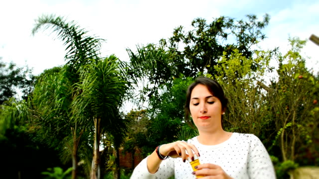 Woman and soap bubbles in park video