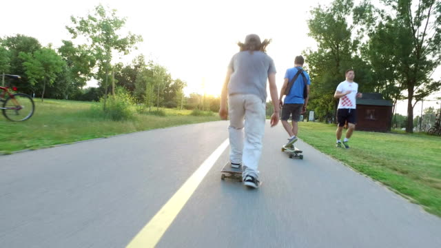 Woman and two men skateboarding on cycling pathway at sunset video