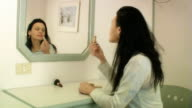 Woman applies lipstick in front of mirror video