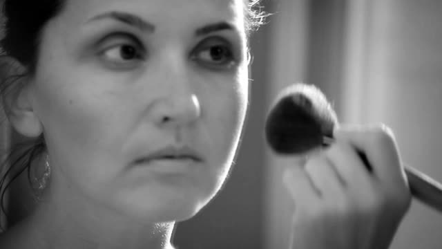 A woman applying make up in front of the mirror video