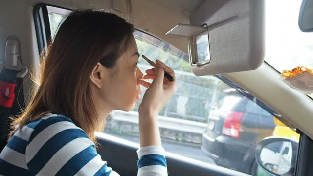 Woman applying makeup in the car video