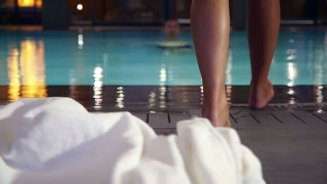 Woman approaching the pool in a hotel video