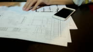 Woman architect working with blueprint sheets, layouts and drawings of the premises video