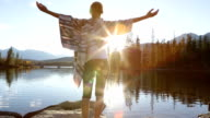 Woman arms outstretched by the lake at sunrise video