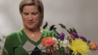 Woman arranging flowers, looking at camera video