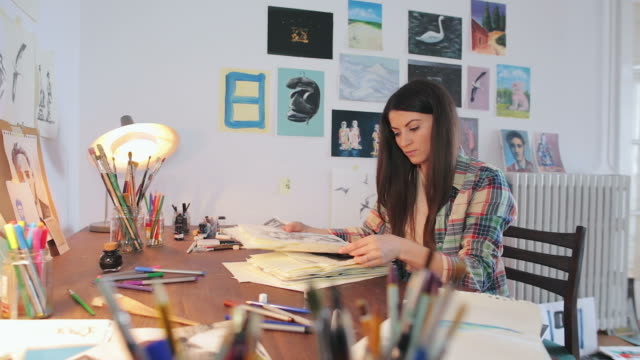Woman artist looking at sketches. video