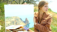 woman artist painting and beautiful coast video
