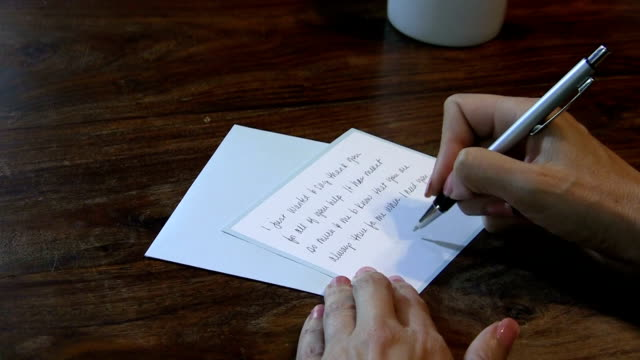 Woman at a desk writing a thank you note video