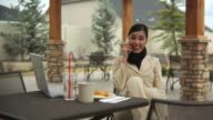 Woman at cafe talking on cell phone video