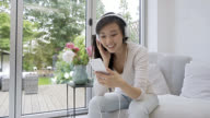 Woman at home listening music with headphones video