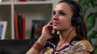 Woman at home listening to music, close up video
