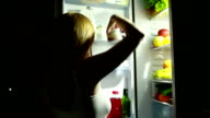 Woman at night looking into fridge. girl takes the orange. video