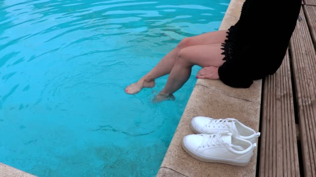 Woman at pool near white sneakers video