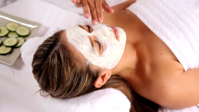 Woman at spa with facial mask and cucumbers video
