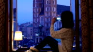 Woman at the window taking photo of Krakow video