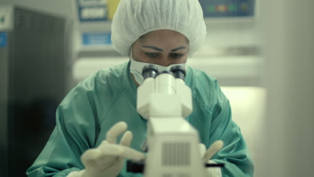 Woman at work with microscope in biotechnology laboratory video