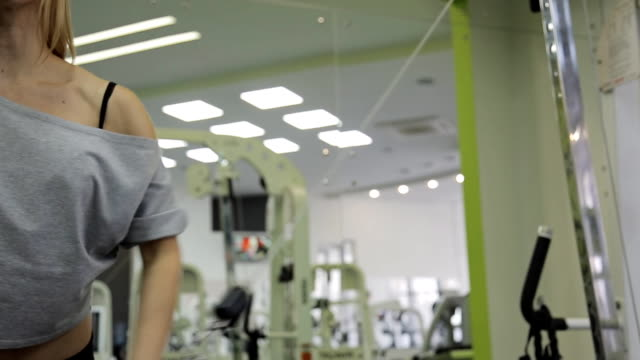 A woman athlete, trains on the chest and front delts shoulder in the gym video