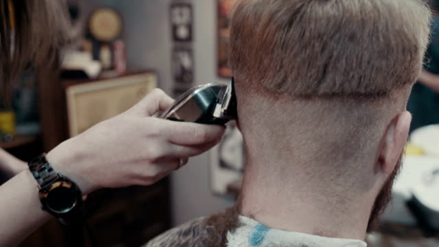 Woman barber cuts the hair of the client with clipper at barbershop video