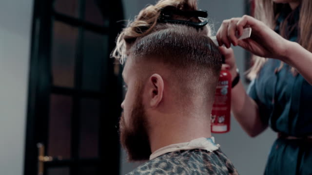 Woman barber cutting hear of client with scissors and comb, close up video