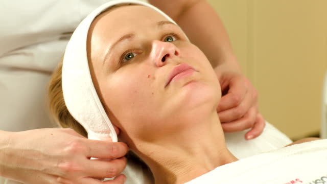 Woman being prepared for facial spa procedures video