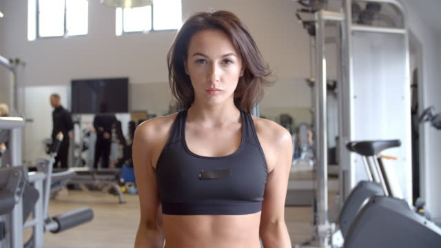 Woman bench working out with dumbbells at a gym, front view video