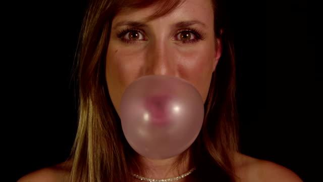 SLOW MOTION: Woman blowing gum bubbles video