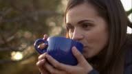 Woman blowing on the tea to cool down. video