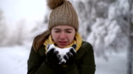 Woman blowing the snow off video