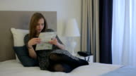 Woman booking her holidays laying on bed with map video